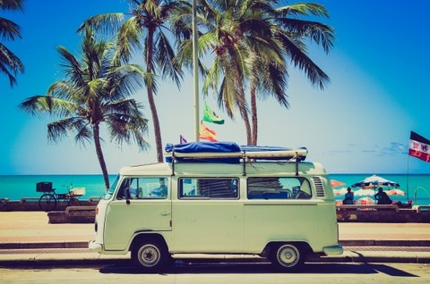 green-camper-on-promenade-with-palm-tree-and-sea-in-background