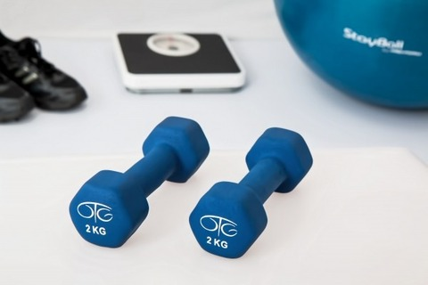 blue-dumbells-with-exercise-ball-and-scale-on-floor