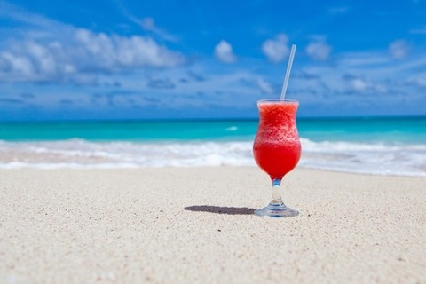 close-up-of-cocktail-drink-with-drinking-straw-on-beach