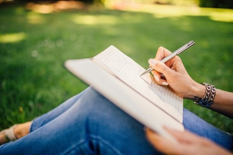 woman-writing-in-netbook-sitting-in-park