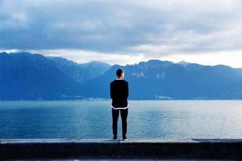 solitude-man-standing-alone-shore-beach-alps