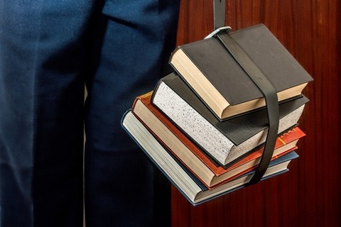 man-carrying-books-in-belt
